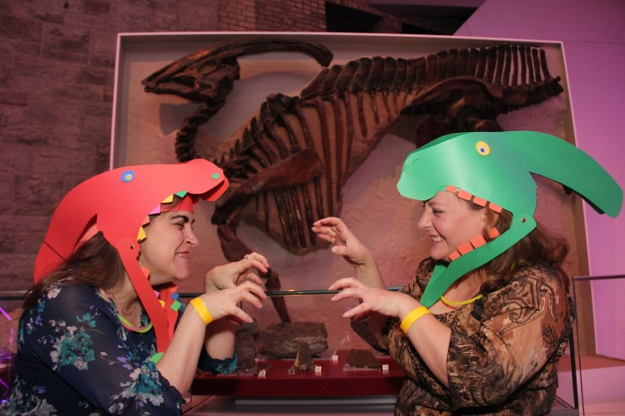 Kathy Zadvorny and Melissa Whitman show off their arts and crafts hadrosaur hats beneath the real deal.
